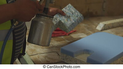 Worker washing a piece of concrete block - Side view mid ...