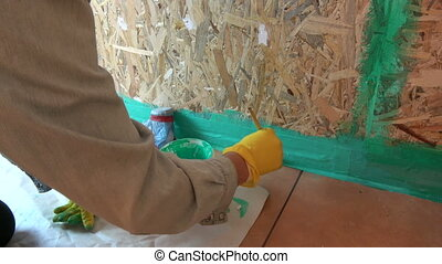 Worker waterproofing wooden bathroom construction - Worker...