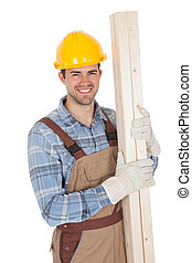 Worker wearing hard hat and holding timber