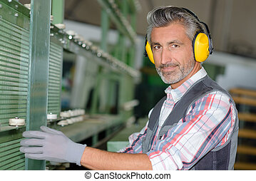 worker wearing hearing protection at a factory