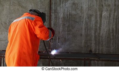 Worker in orange clothes weld metal gratings by acetylene torch, close-up view