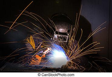worker welding in production line
