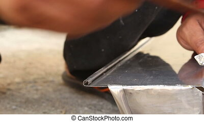 worker welding roofer stainless gutter - close up worker...