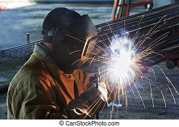 worker welding with electric arc electrode - welder worker...