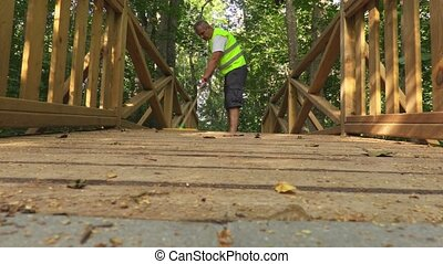 Worker wiped a wooden bridge with a brush