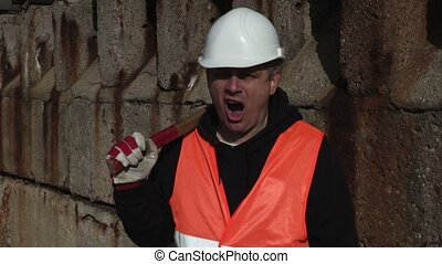 Worker with a hammer on his shoulder