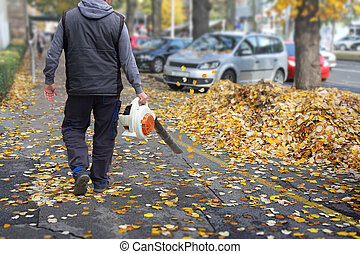 Worker with a leaf blower - Worker on a street in autumn ...