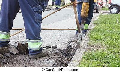 Worker with a shovel collects broken asphalt behind jackhammer
