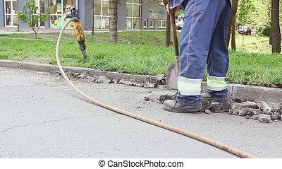 Worker with a shovel collects broken asphalt