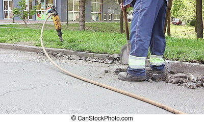 Worker with a shovel collects broken asphalt - View on...