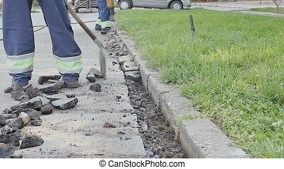 Worker with a shovel collects broken asphalt behind...
