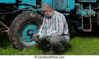 Worker with adjustable wrench thinking near tractor