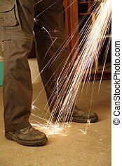 Worker with angle grinder only feet