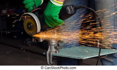 Worker with angular grinding machine is cutting the metal and a lot of sparks flying around