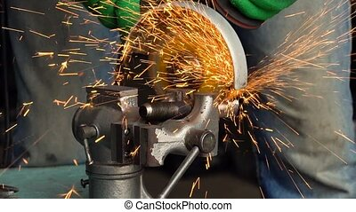 Worker with angular grinding machine is cutting the metal and a lot of sparks flying around. Slow motion
