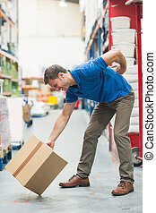 Worker with backache while lifting box in warehouse - Side...