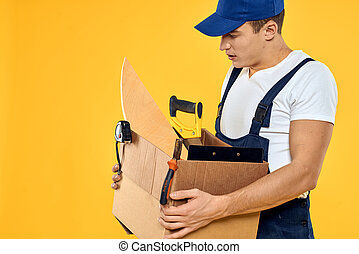 worker with box in hand tools loader yellow background
