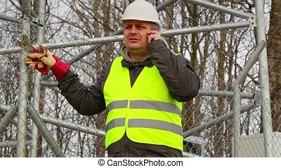 Worker with cell phone and adjustable wrench at outdoors
