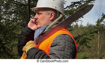 Worker with cell phone and machete in forest