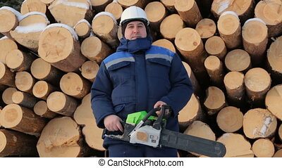 Worker with chain saw against pile of logs