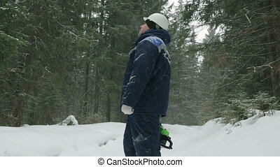 Worker with chain saw going through the winter forest