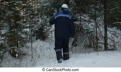 Worker with chain saw on shoulder going through winter...