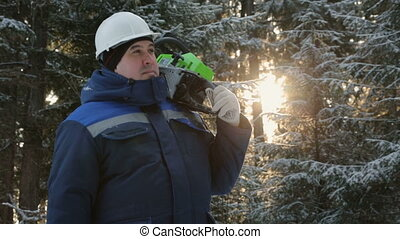 Worker with chainsaw on shoulder looking around in winter...