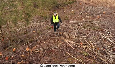 Worker with chainsaw on steep forest slope