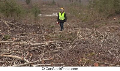 Worker with chainsaw walking through steep forest slope