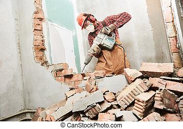 worker with demolition hammer breaking interior wall