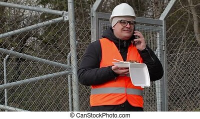 Worker with food talking on smart