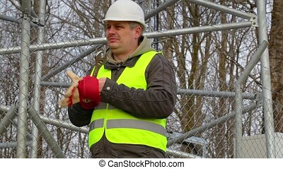 Worker with gloves and adjustable wrench at the fence
