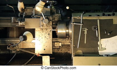 Worker with gloves to adjust the lathe when manufacturing parts.