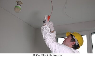 worker with helmet installing smoke detector on the ceiling
