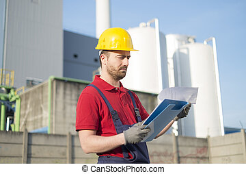 Worker with helmet working outside a modern factory