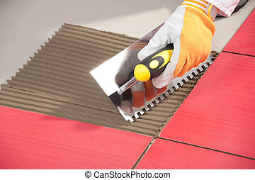 Worker with notched trowel install red tiles with tile...