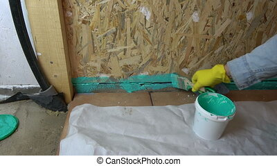 Worker with paintbrush waterproofing bathroom construction -...