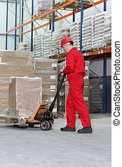 worker with pallet jack - worker in red uniform at work with...