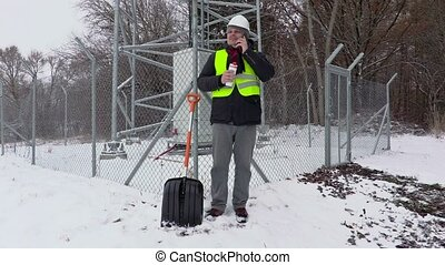 Worker with phone and thermos near snow shovel and fence