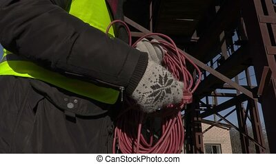 Worker with power cord near metal tanks