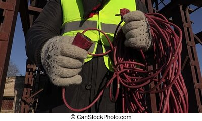 Worker with power cord near tanks
