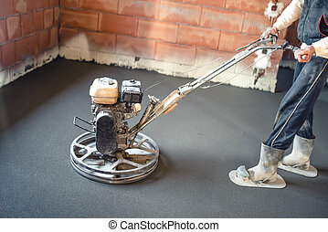 Worker with power trowel tool finishing concrete floor, smooth concrete surface.