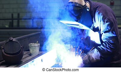 Worker with protective mask welding metal. factory