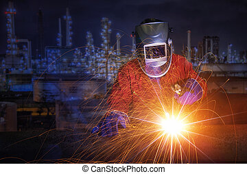 worker with protective mask welding metal and sparks in oil...