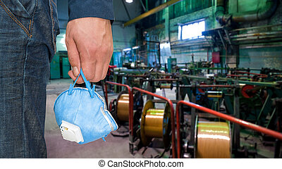 Worker with protective respirator at man hands at industrial...