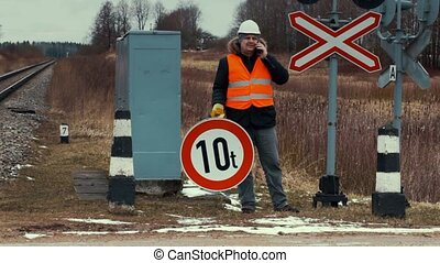 Worker with road sign on the railway crossing