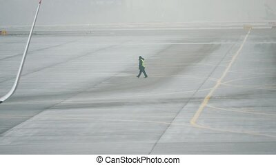 Worker with safety clothes walking on the runway at international airport, telephoto shot