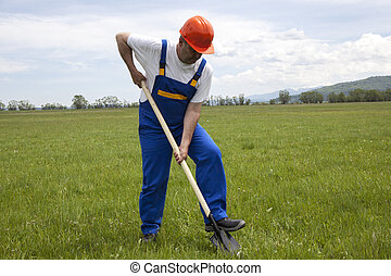 Worker with Shovel on a Green Lawn