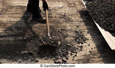 Worker with shovel taking asphalt.