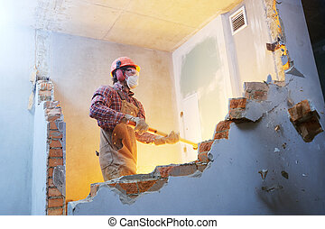 worker with sledgehammer at indoor wall destroying - Worker...